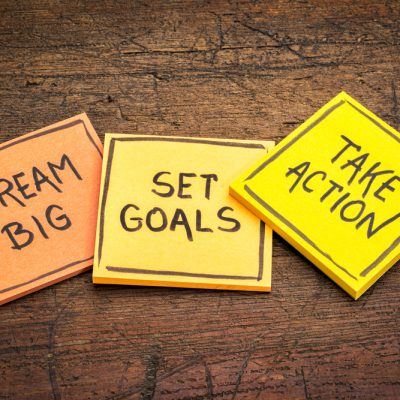 dream big, set goals, take action - motivational advice or reminder on colorful sticky notes against rustic wood